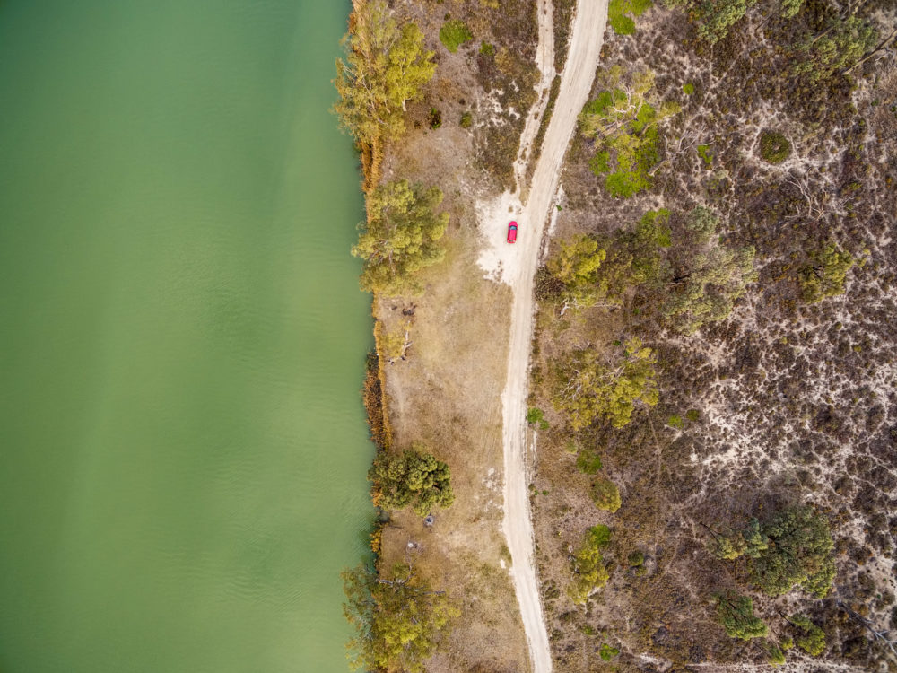 Looking down at small red car parked on the shore of Murray River in South Australia - aerial view