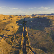 Aerial panorama of straight rural road passing through countryside at sunset