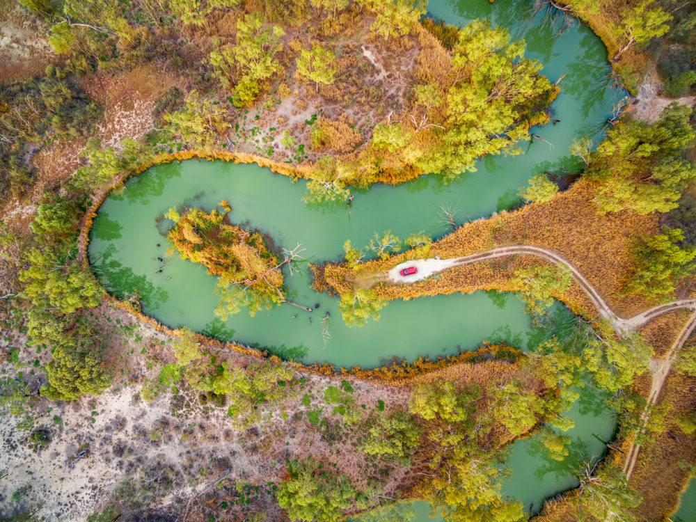Looking down at red car on the shore of magnificent meandering Murray River. Riverland, South Australia, aerial view.