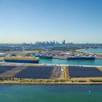 Aerial Panorama of Port Melbourne with docked Carr Carriers, Yarra River, and Melbourne CBD skyline on the horizon. Melbourne, Victoria, Australia