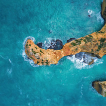 Looking down at turquoise ocean waves breaking over rocks - aerial view