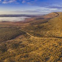 Aerial panorama of winding dirt road in Flinders Ranges hills at sunrise. Hawker, South Australia