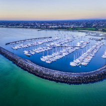 Magnificent wide aerial panorama of a beautiful Marina with moored sailboats and Melbourne coastline at dusk