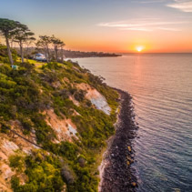 Beautiful trees on a green hill near the ocean at sunset - aerial view