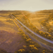 Aerial panorama of Hume Highway passing through scenic countryside at sunset in Australia