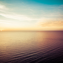 Aerial view of sun setting over ocean. Nothing but skies and water. Beautiful tranquil scene