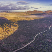 Aerial panoramic landscape of gravel road passing through Flinders Ranges hills and native vegetation at sunset in South Australia