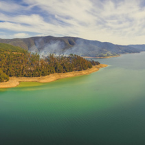 Aerial panorama of smoke rising from forest on beautiful lake shore