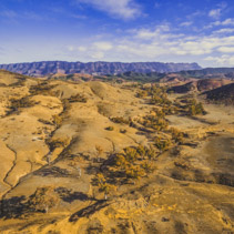 Aerial view of Flinders Ranges mountains and rolling hills with trees in South Australia