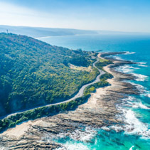 Great Ocean Road passing along scenic coastline - aerial view