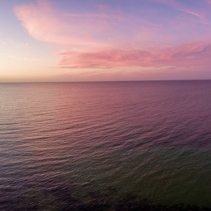 Aerial panorama of sunset over ocean. Nothing but sky, clouds and water. Beautiful serene scene
