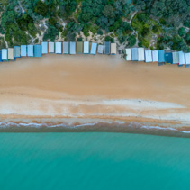 Looking down at beach huts sandy beach, and turquoise bay water at Mount Martha, Melbourne, Australia