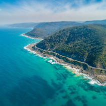 Aerial landscape of Great Ocean Road and scenic green hills on sunny day in Victoria, Australia