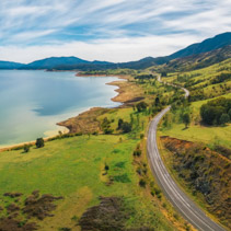 Road winding through lake shore and mountains. Scenic aerial panorama of Australia