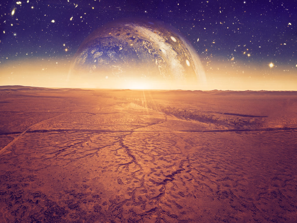 Alien landscape - planet rising over dry cracked desert land. Elements of this image are furnished by NASA#