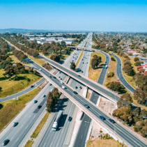 Straight highway passing through interchange in Melbourne, Australia - aerial view