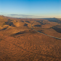 Wide aerial panorama of rural road passing through Martian landscape at sunset