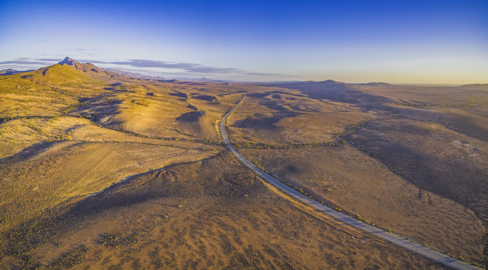 Rural road passing through dry land with scarce peaks at sunset - aerial view