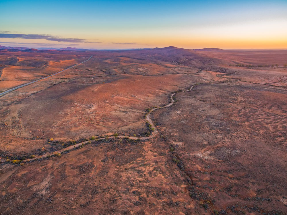 Aerial view of sunset over alien martian-like red landscape with winding gravel road