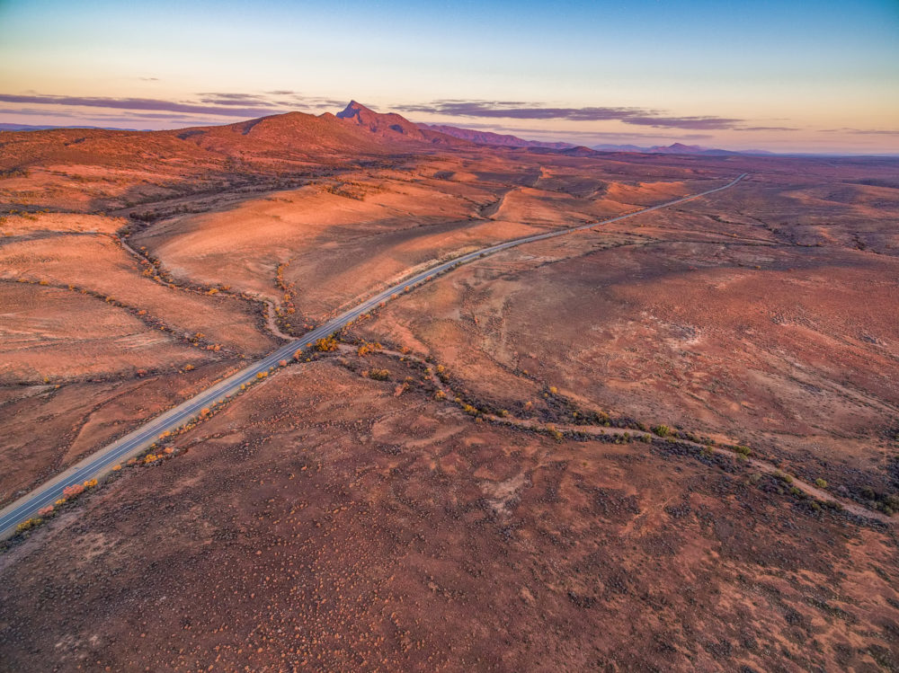 Scenic aerial landscape of orange sunset over dry red land and mountains