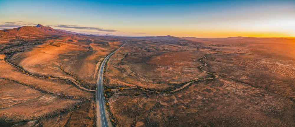 The Outback Highway passing through Flinders Ranges at dusk - aerial panorama
