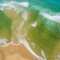 Aerial view looking down at turqouise ocean waves and sandy beach