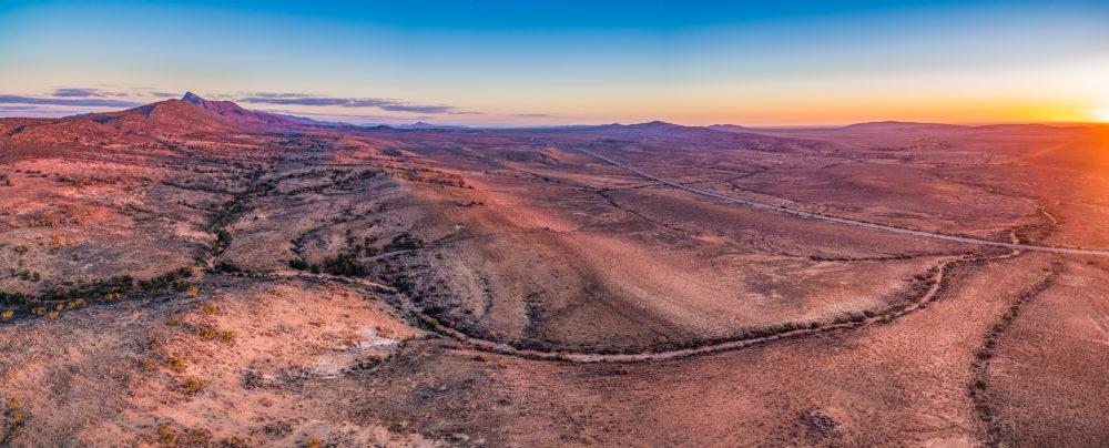 Aerial panoramic landscape of sunset sun flare over alien landscape of Flinders Ranges in South Australia