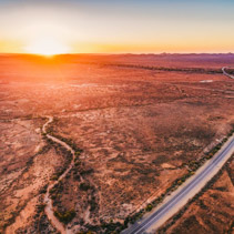 Orange sunset over dry land and rural highway winding through in South Australia