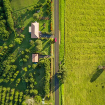 Aerial view - looking down at red car driving on rural highway among green grass and countryside houses at sunset