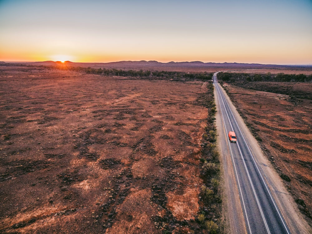 Red car driving on rural road passing through Australian outback leading to Flinders Ranges peaks at sunset