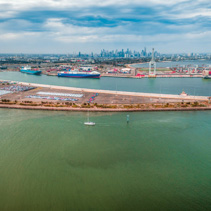 Aerial view of Port Melbourne with moored cargo vessels and Melbourne CBD skyline on the horizon