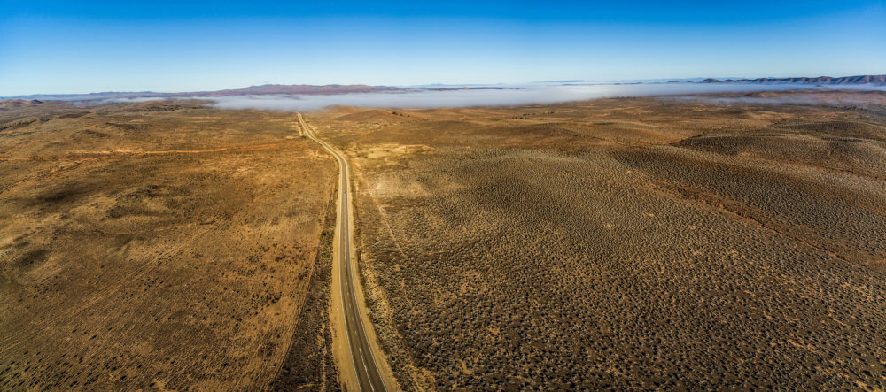 Rural highway passing through Australian outback desert leading to mountains under low cloud - aerial panorama