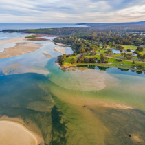 Aerial view of Mallacoota town and coastline at sunset in Australia