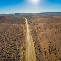 Rural road passing through dry land with scarce vegetation on bright sunny day - aerial view
