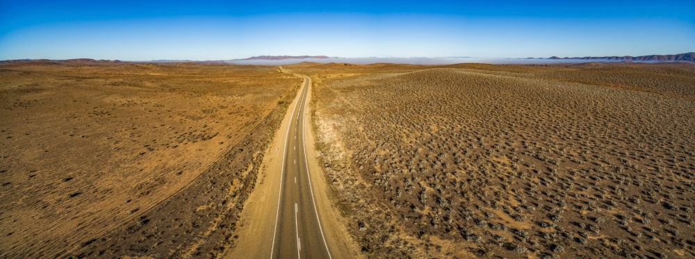 Rural road passing through dry land with scarce vegetation at sunrise - wide aerial panorama