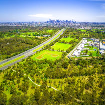 Aerial view of green parkland, Melbourne Polytechnic, and Melbourne CBD skyscrapers in the distance on summer day