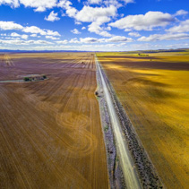 Straight gravel road passing through agricultural fields under beautiful clouds leaving shadows on land - aerial view