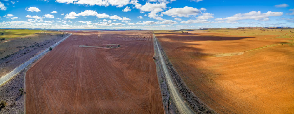 Wide aerial panorama of agricultural fields under beautiful blue sky with white fluffy clouds