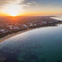 Aerial view of sunrise at Brighton Beach showing the suburb and bathing boxes. Melbourne, Victoria, Australia