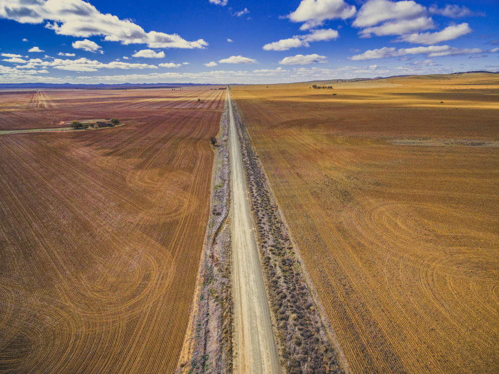Straight dirt road leading to the horizon between plowed fields in Australian countryside