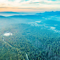 Beautiful sunset over mountains and forest with road passing through - aerial view