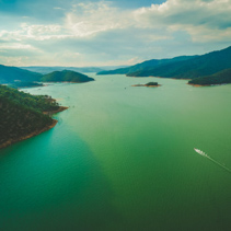 Aerial view of lonely boat sailing on beautiful lake among hills at sunset