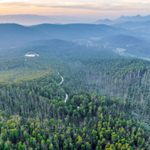 Scenic sunset over mountains with road passing through forest in Australia - aerial view