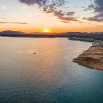 Tiny boat in a big lake at sunset - aerial panorama with copy space