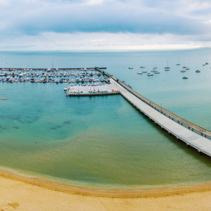 Aerial panorama of long pier leading to moored boats at marina. Beautiful turquoise water and beach
