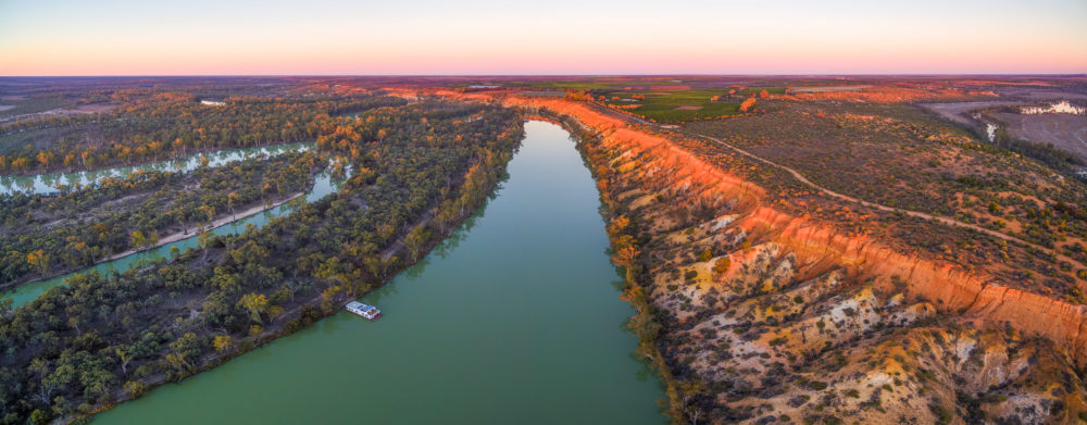 Aerial panorama of sandstone cliffs over Murray RIver and moored houseboat at sunset