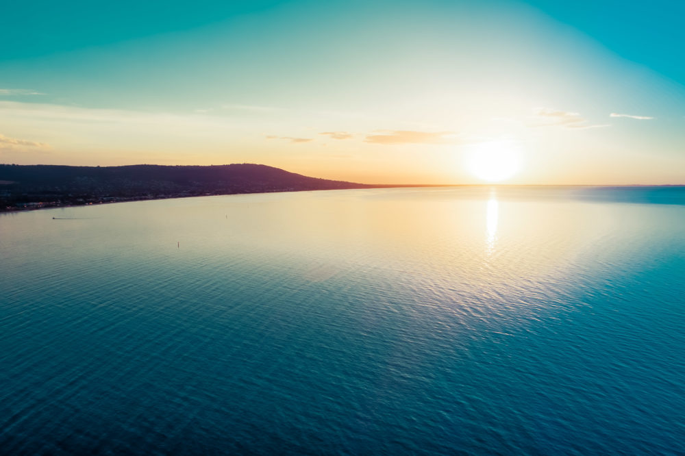 Dreamy sunset over ocean coastline - aerial view with copy space