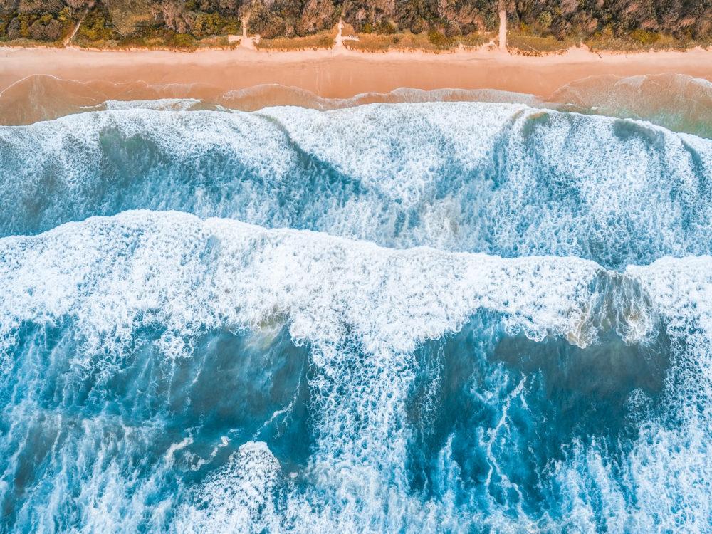 Looking down at large ocean waves breaking on a coastline