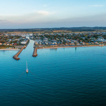 Aerial panorama of Mornington Peninsula coastline and sailboat approaching waterway entry at dusk
