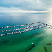 Aerial seascape of moored boats in marina and beautiful turquoise bay waters at sunrise
